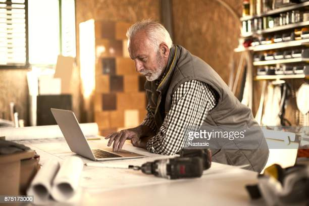mature designer looking at laptop - only senior men stock pictures, royalty-free photos & images