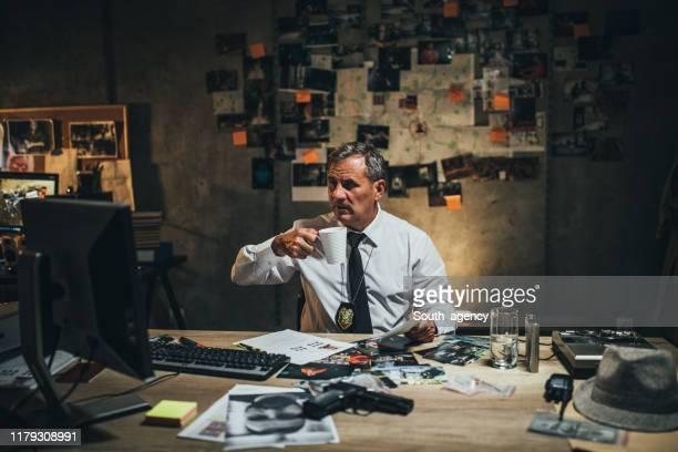 détective mûr examinant des preuves - malfaiteur photos et images de collection