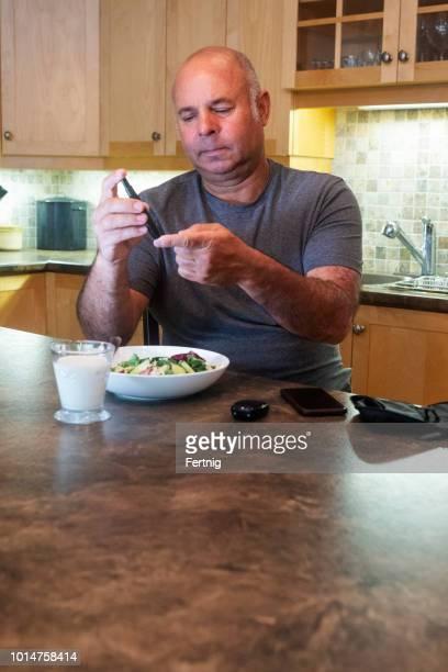 Mature diabetic man testing his blood sugar at home.