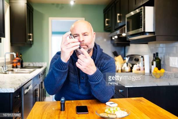 Mature diabetic patient at home testing his blood sugar.