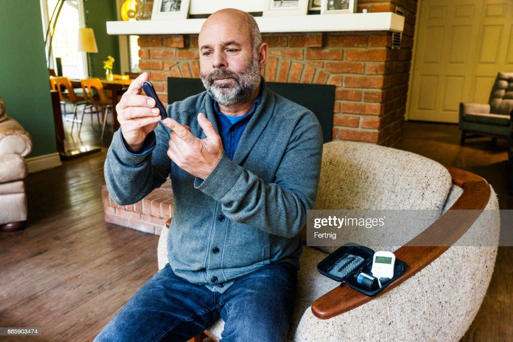 Mature diabetic patient taking a blood test : Stock Photo