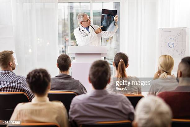 Mature doctor analyzing an X-ray image on education event.