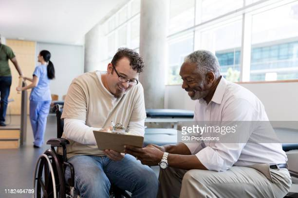 mature doctor and male patient smile as patient signs paperwork - demonstration stock pictures, royalty-free photos & images