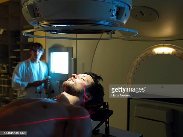 Mature doctor by male patient lying on radiology bed