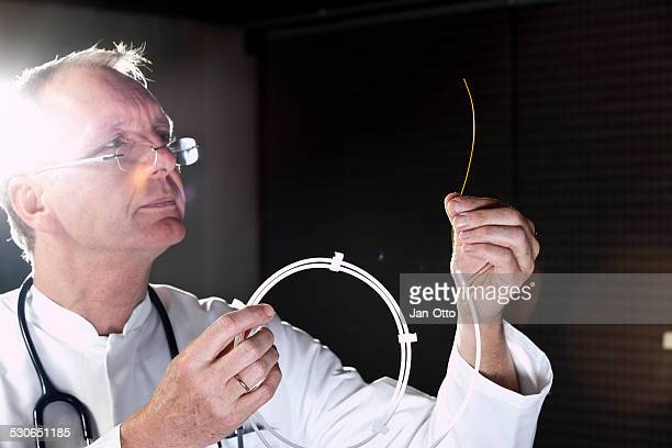 Mature doctor demonstrating catheter