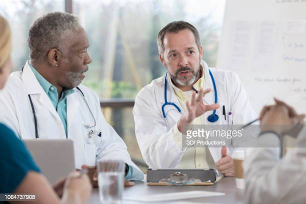 Mature doctor discusses serious topic with colleagues