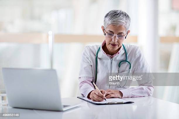 Mature doctor filling medical documents at doctor's office.