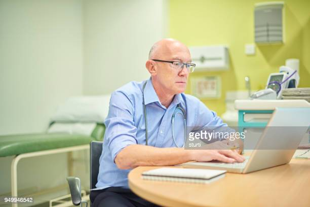 mature doctor in his office - doctor's surgery stock pictures, royalty-free photos & images