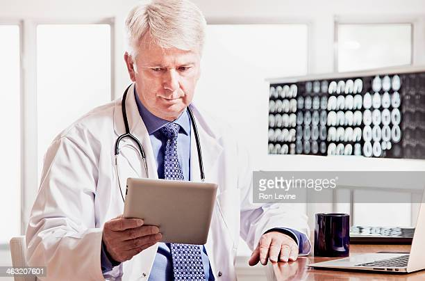 Mature doctor looking at digital tablet