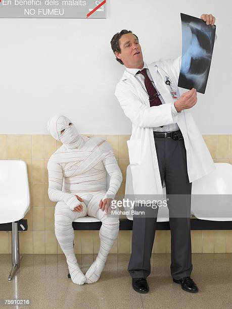 mature doctor looking at x ray with bandaged patient - outpatient care stock pictures, royalty-free photos & images