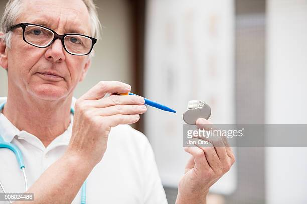 Mature doctor pointing at a cardial pacemaker