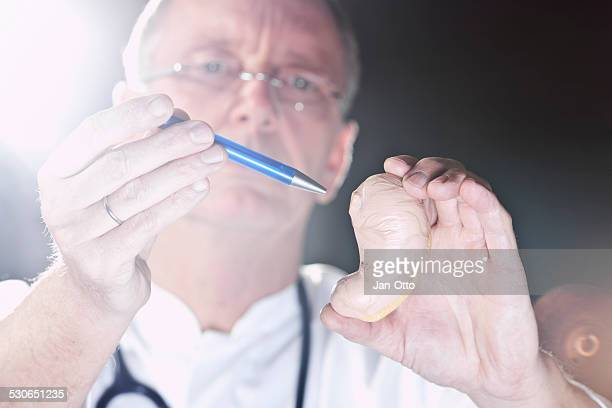 Mature doctor pointing at gaster