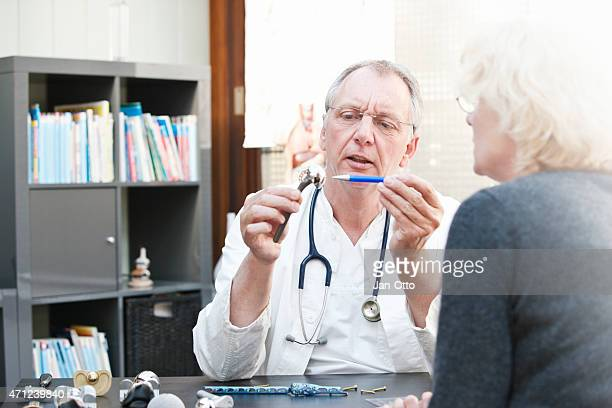 Mature doctor presenting shoulder prosthesis to female patient