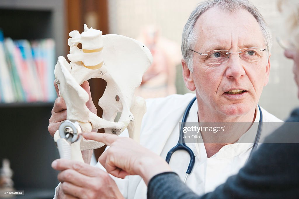 Mature doctor presenting total hip arthroplasty to female patient : Stock Photo