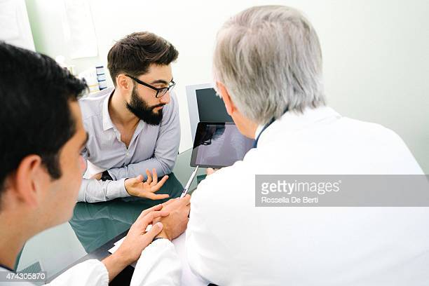 Mature Doctor Showing His Patient Chest X-Rays On Digital Tablet