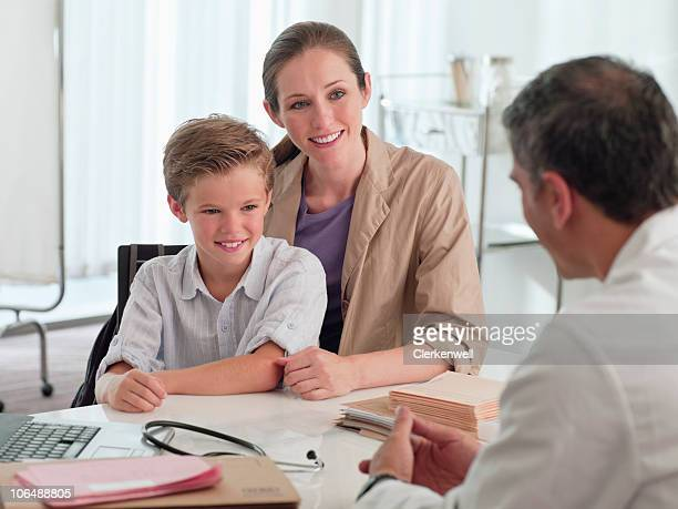 Mature doctor talking to mother and son (10-11) in clinic