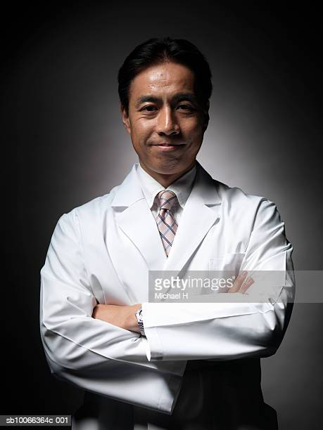 Mature doctor with arms crossed, smiling, portrait, close-up