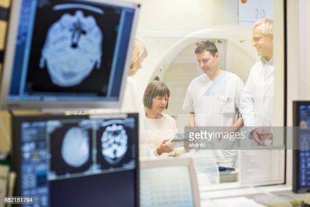mature doctors analyzing reports with senior woman - hospital machine stock photos and pictures