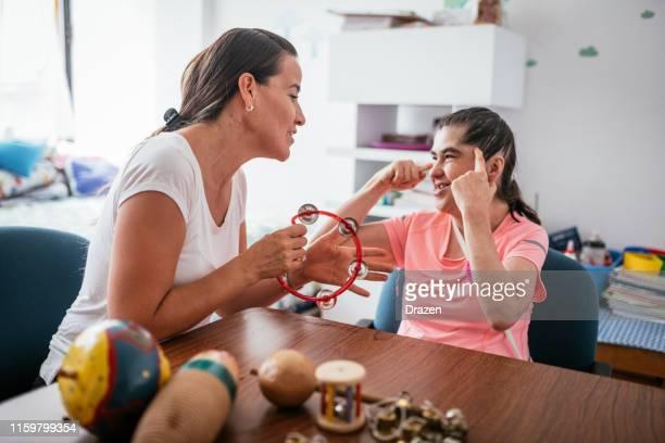 mujer madura síndrome de down en la guardería de la guardería, cantando con el maestro - discapacidad intelectual fotografías e imágenes de stock