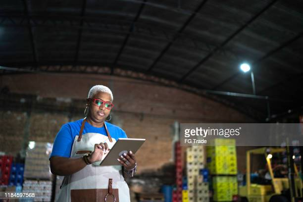 mature employee using digital tablet at warehouse - market retail space stock pictures, royalty-free photos & images