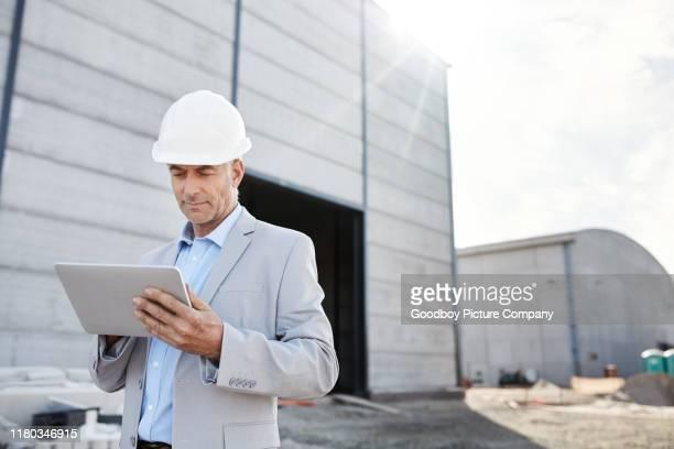 ausgereifter ingenieur mit seinem digitalen tablet auf einer baustelle - vorarbeiter stock-fotos und bilder