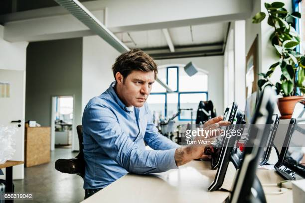Mature engineer working on touch screen panels in his office
