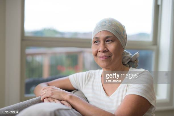 mature ethnic woman with cancer wearing headwrap on couch - cancer stock photos and pictures