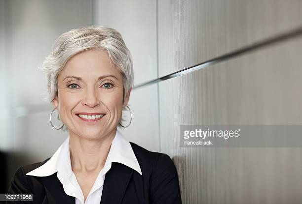 mature executive business woman smiling - president stockfoto's en -beelden