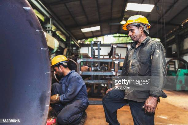 mature factory employee overseeing the finishing touches on a metal pipe - india stock pictures, royalty-free photos & images