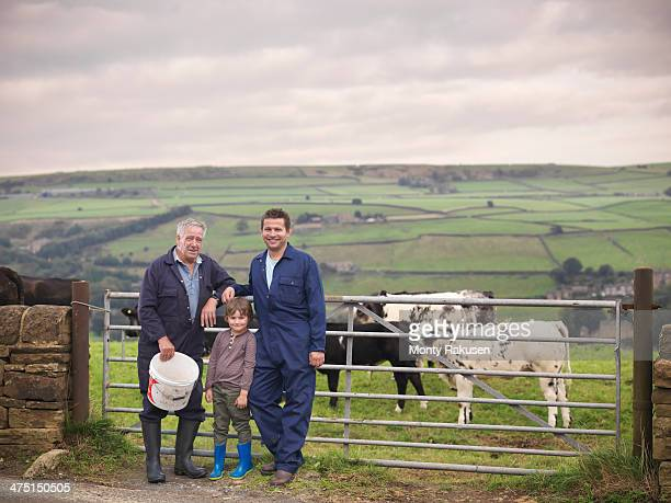 Mature farmer, adult son and grandson standing together at gate to cow field, portrait