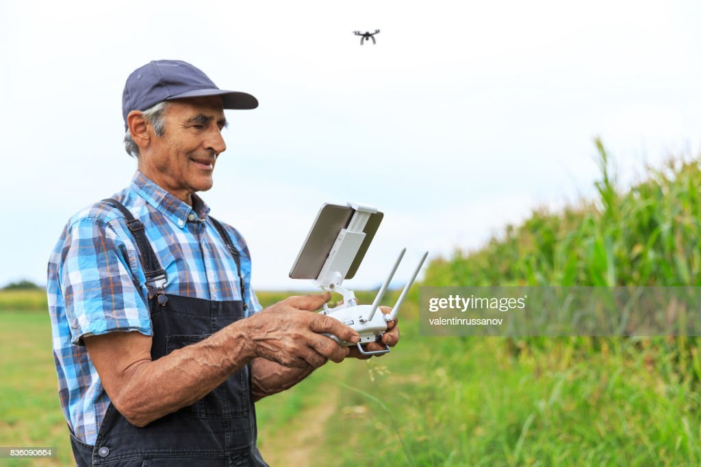 Mature farmer flying a drone over a field : Stock Photo