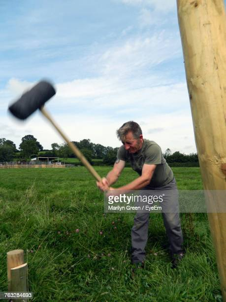 Mature Farmer Hammering Wooden Post While Standing On Field