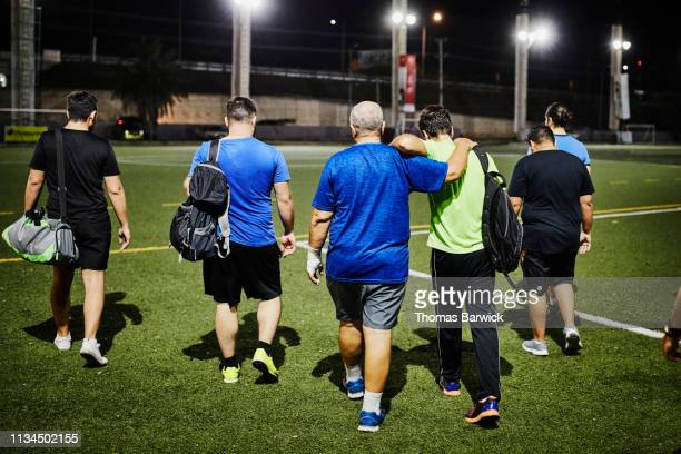 mature father and adult son walking off soccer field after evening game with friends - mid adult men fotografías e imágenes de stock