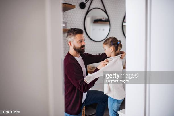mature father and his small daughter in bathroom indoors at home, getting dressed. - getting dressed stock pictures, royalty-free photos & images