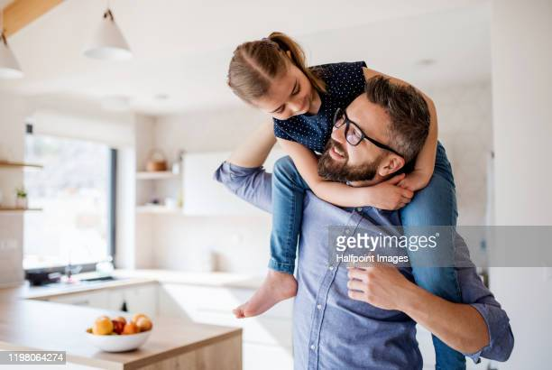 mature father giving piggyback ride to small daughter indoors at home. - family with one child stock pictures, royalty-free photos & images