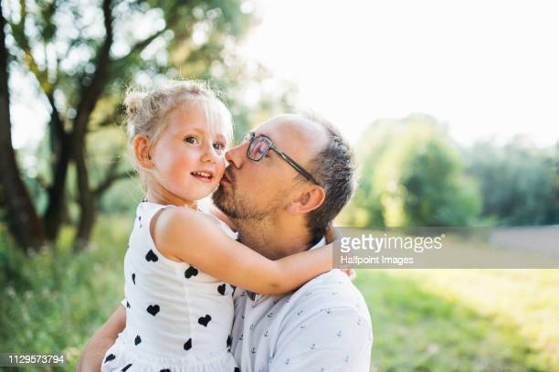 A mature father kissing a cheerful toddler daughter outdoors in nature in summer.