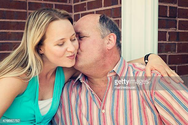 Mature father kissing adult daughter's cheek outdoors.