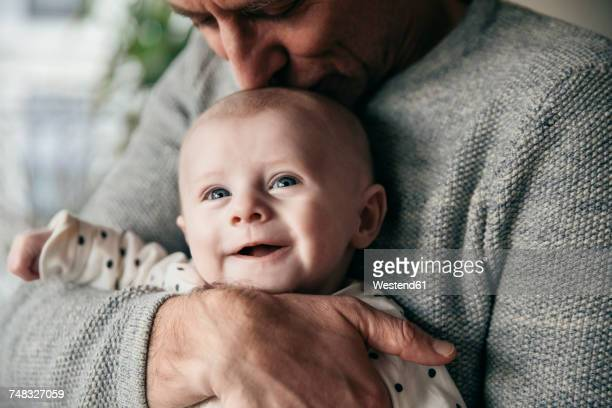 mature father kissing laughing baby on its head - 2 5 mesi foto e immagini stock