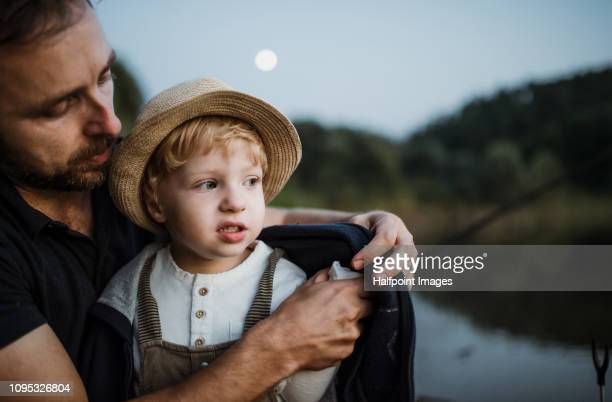 a mature father putting a coat on a toddler son outdoors by a lake at night. - mini moon stock pictures, royalty-free photos & images