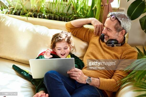 mature father watching online tv with daughter in dinosaur costume - family stock pictures, royalty-free photos & images
