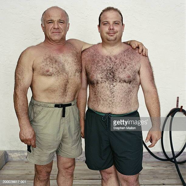 mature father with arm around son, portrait - hairy chest stock-fotos und bilder