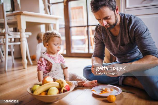 mature father with small toddler daughter sitting on the floor indoors, eating fruit. - family at home stock pictures, royalty-free photos & images