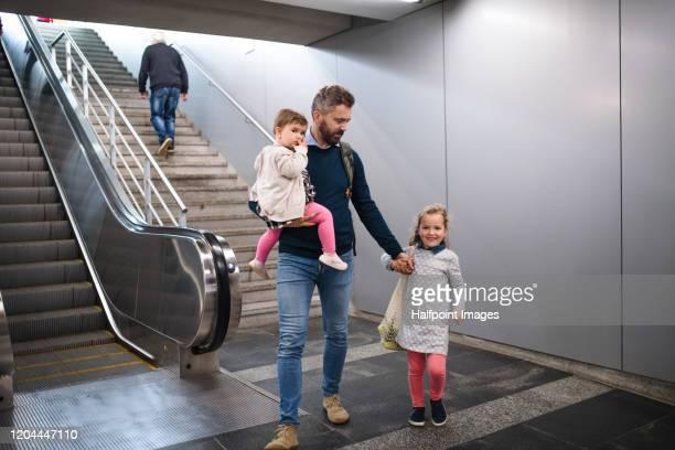 mature father with two small daughters walking by escalators indoors in city. - tvåbarnsfamilj bildbanksfoton och bilder