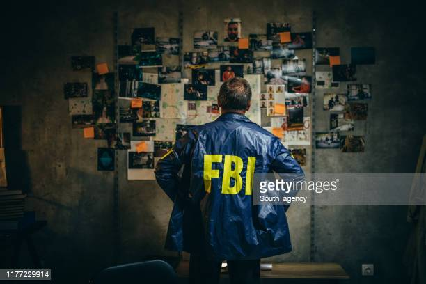 mature fbi agent works on a case alone - murder stock pictures, royalty-free photos & images