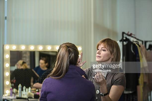 Mature female artist applying make-up to model at studio