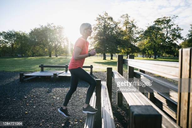 mature female athlete doing step-ups in outdoor fitness area - clapham common stock pictures, royalty-free photos & images
