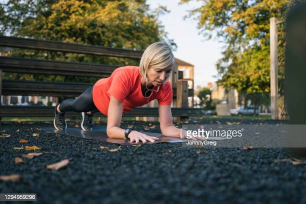mature female athlete in forearm plank position at park - clapham common stock pictures, royalty-free photos & images