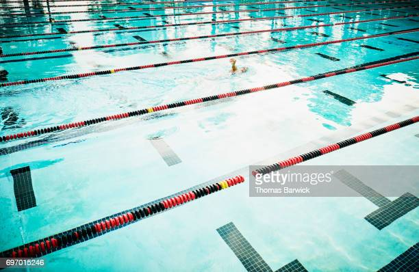 Mature female athlete swimming alone in outdoor pool during early morning workout