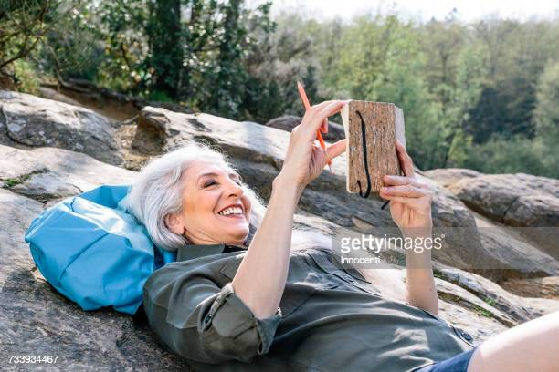 Mature female backpacker reclining on rock in forest, Scandicci, Tuscany, Italy