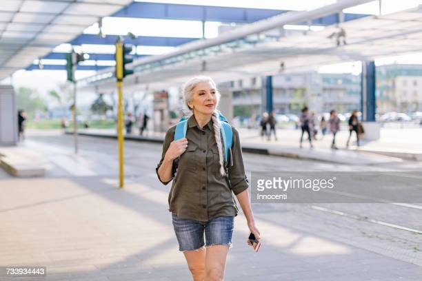 Mature female backpacker walking in bus station, Scandicci, Tuscany, Italy